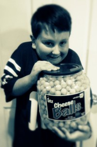 SK hugging huge bucket of cheese balls with sinister yet goofy expression