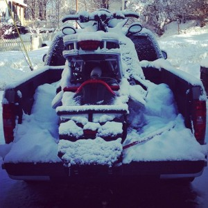 Snow-covered sled in bed of truck
