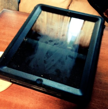 Very grubby iPad with debris stuck to it and a smeared screen