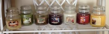 Seven Yankee Candle jars on a shelf