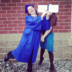 Teen in cap & gown with diploma