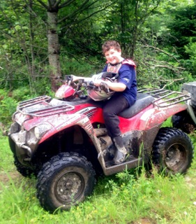 Short Kid sitting on his four-wheeler on the side of the trail