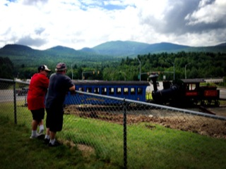 Short Kid and his dad looking at a train