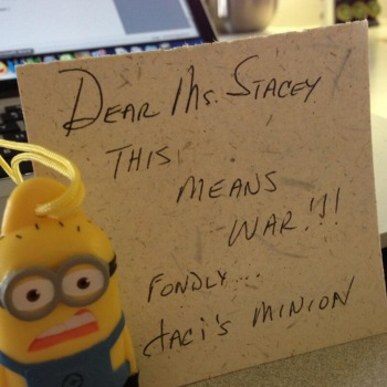 Minion with scared expression holding sticky note