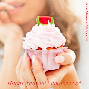 Cute pink cupcake being held out by impossibly gorgeous manicured hand