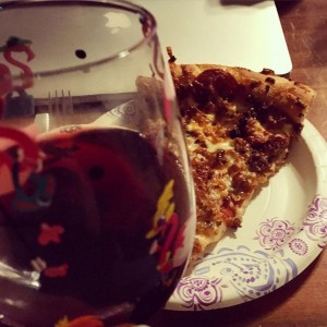 A glass of red wine in front of a plate of pizza with laptop in background