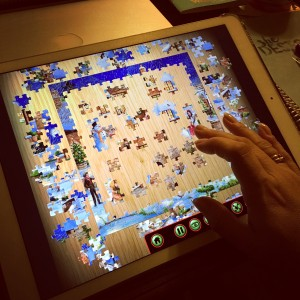 Picture of jigsaw puzzle app on iPad with laptop lurking in the background
