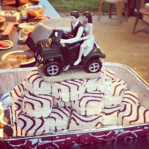 A pyramid of Little Debbie Zebra Cakes topped by a bride and groom riding a ceramic ATV