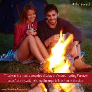 Ridiculously attractive couple sitting on the ground and smiling at a blazing campfire