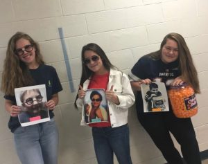 Three high school girls dressed up as the three photos of my son, holding printed out copies. A girl with long, blonde hair wearing a blue tee and Harry Potter glasses. A girl with long brown hair wearing a coat with the collar flipped up like Miami Vice and aviator shades. And a girl with long brown hair wearing a Tom Brady jersey and hugging a bucket of cheeseballs