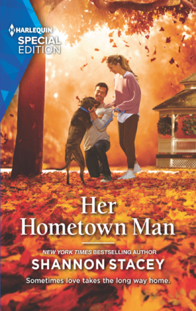 The cover shows a smiling couple playing with a dog against a vibrant autumn background, with fall foliage around them and fallen on the ground. The woman has a long blonde ponytail and is casually dressed in a slouchy pink sweater layered over a white tee, with darker pink jogger pants and white sneakers. She has her hand on the shoulder of a dark-haired man in a long-sleeve gray tee and jeans who is down on one knee petting a large dark brown dog. There's a large gazebo in the background.